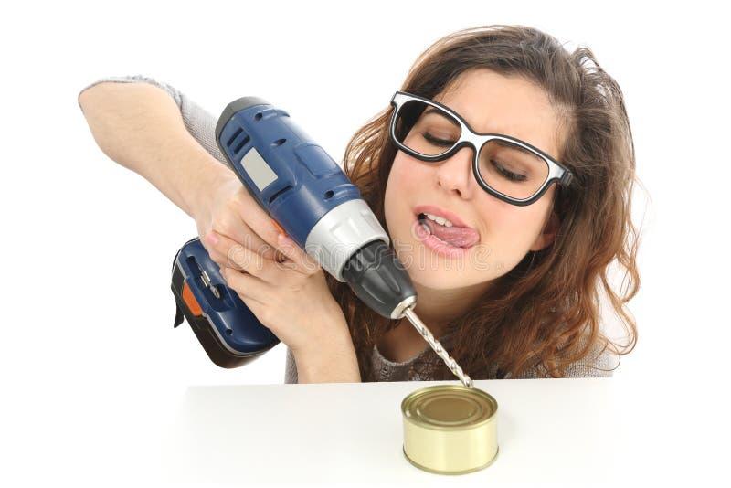 Grappig geekmeisje die een tin met een boor proberen te openen royalty-vrije stock foto's