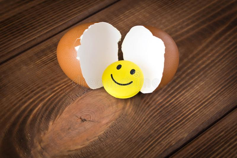 Grappig geel smileystuk speelgoed in een eierschaal Op een houten achtergrond royalty-vrije stock afbeeldingen