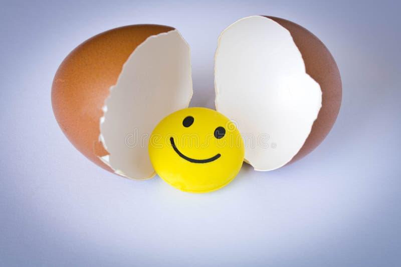 Grappig geel smileystuk speelgoed in een eierschaal Op witte achtergrond royalty-vrije stock afbeelding