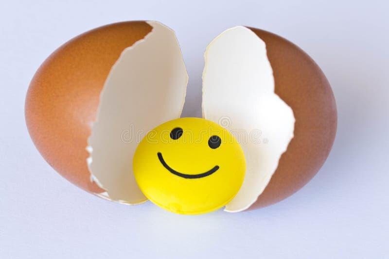 Grappig geel smileystuk speelgoed in een eierschaal Op witte achtergrond royalty-vrije stock afbeeldingen