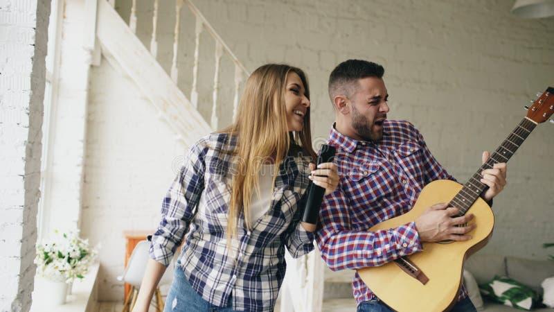 Grappig gelukkig en houdend van paar die en het spelen gitaar dansen De man en de vrouw hebben pret thuis tijdens hun vakantie stock afbeelding