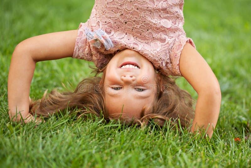 Grappig gelukkig meisje die zich op haar hoofd bevinden stock foto
