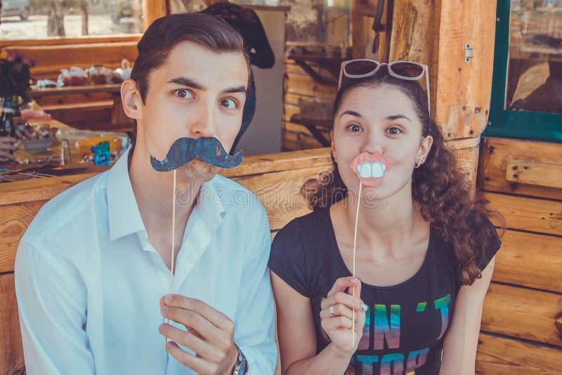 Grappig gelukkig paar die gebruikend de steunen van de fotocabine stellen Movember royalty-vrije stock afbeeldingen