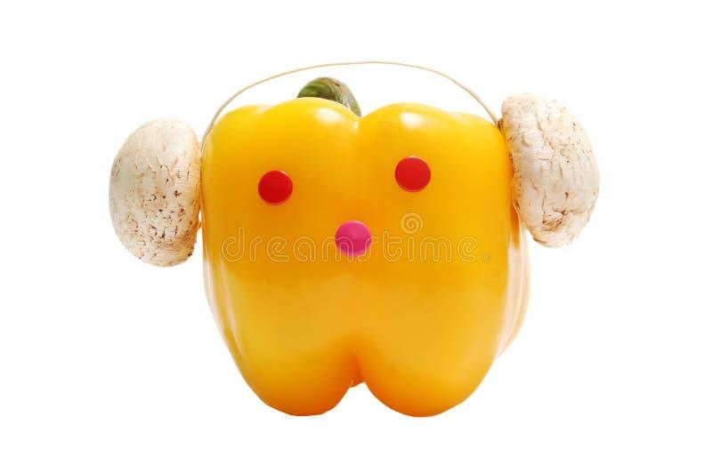 Grappig gezicht met hoofdtelefoons van gele paprika stock afbeeldingen
