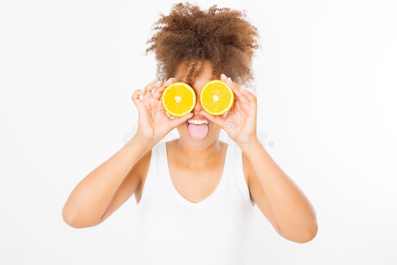 Grappig gezicht met uit tong Mooie jonge Afrikaanse Amerikaanse vrouw met oranje die fruit op witte achtergrond wordt geïsoleerd  stock afbeeldingen