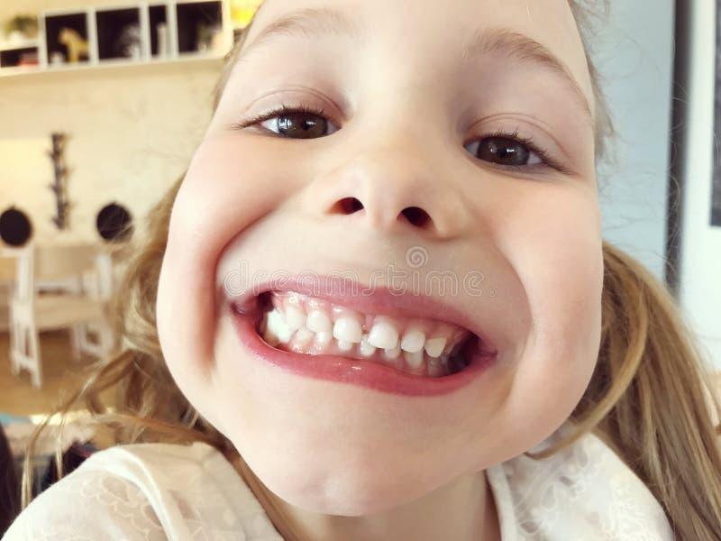 Grappig gezicht van klein meisje met witte tanden stock foto