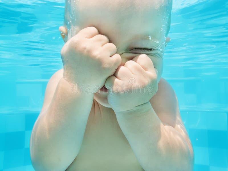 Grappig gezichtsportret van babyjongen het zwemmen en onderwater duiken stock foto
