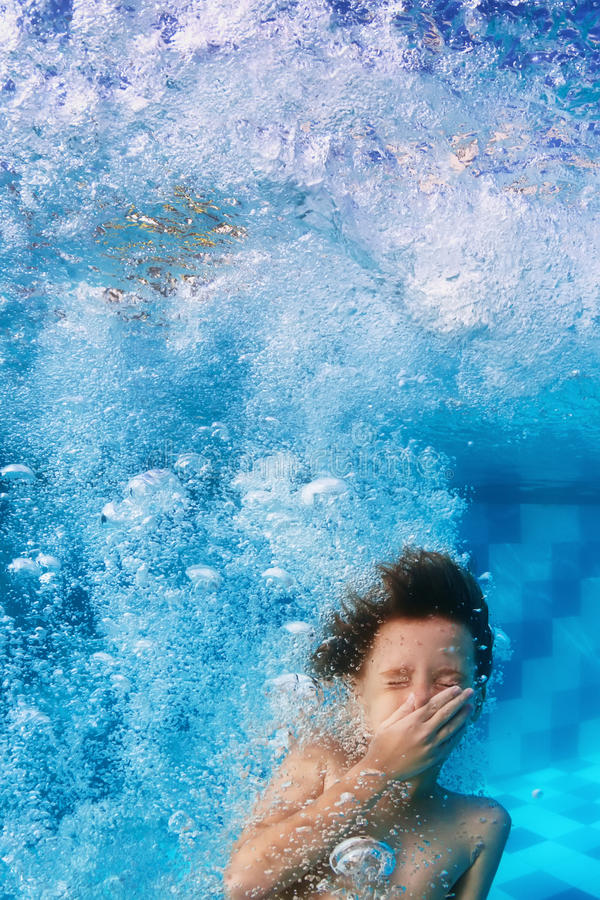 Grappig gezichtsportret van het glimlachen kind zwemmen onderwater in pool stock foto