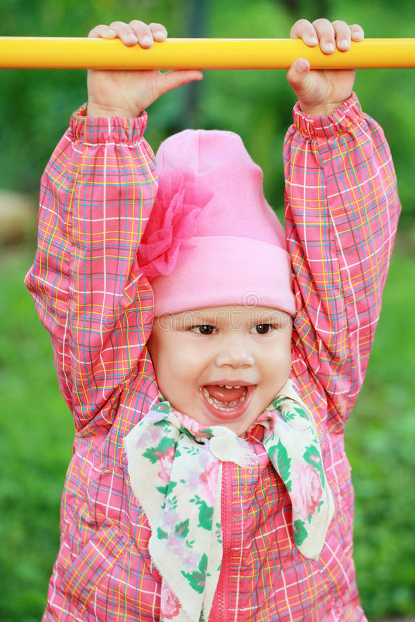 Grappig glimlachend Kaukasisch babymeisje in roze stock foto's