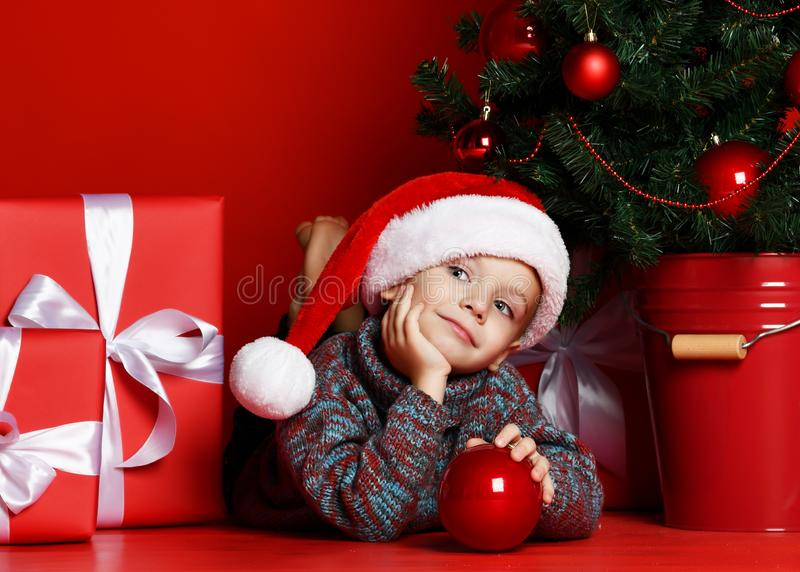 Grappig glimlachend kind in Kerstman rode hoed die op Kerstboomachtergrond liggen royalty-vrije stock afbeeldingen