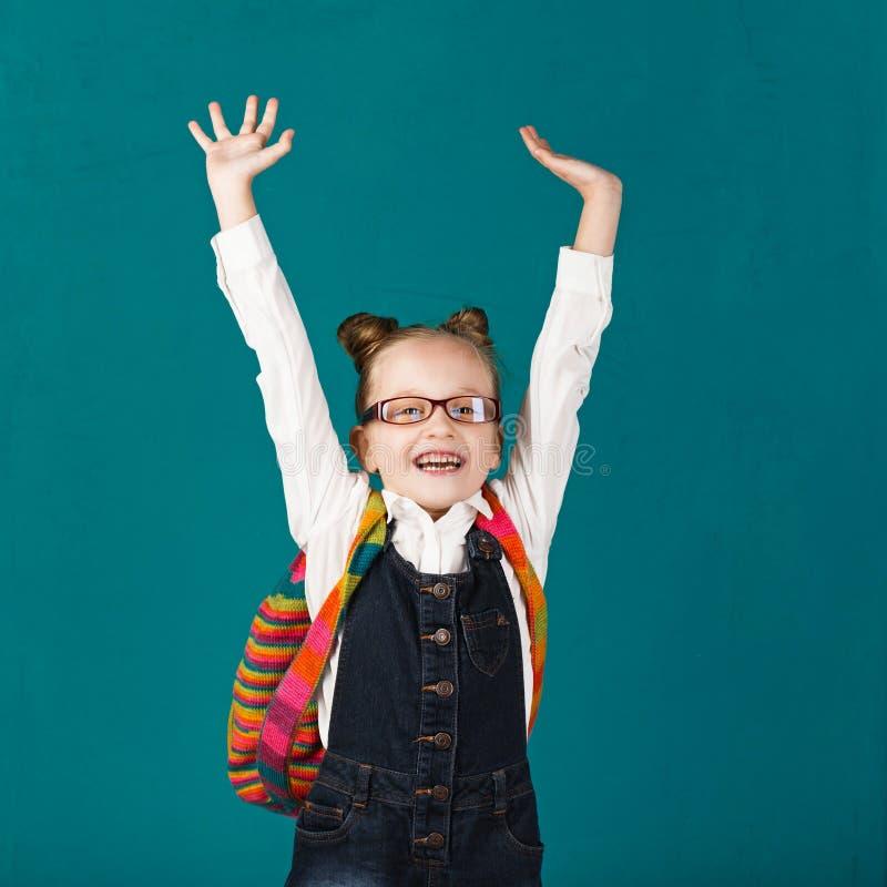 Grappig glimlachend meisje met grote rugzak die en F springen hebben stock afbeeldingen