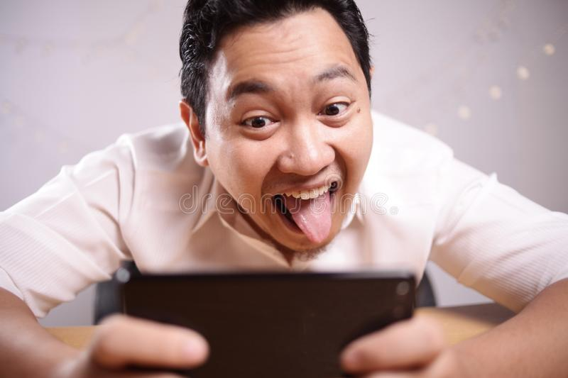 Grappig Jong Aziatisch Guy Playing Games op Tabletsmartphone royalty-vrije stock foto's