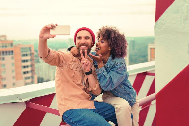 Grappig jong paar die belachelijke gezichten maken terwijl samen het nemen selfies stock foto's