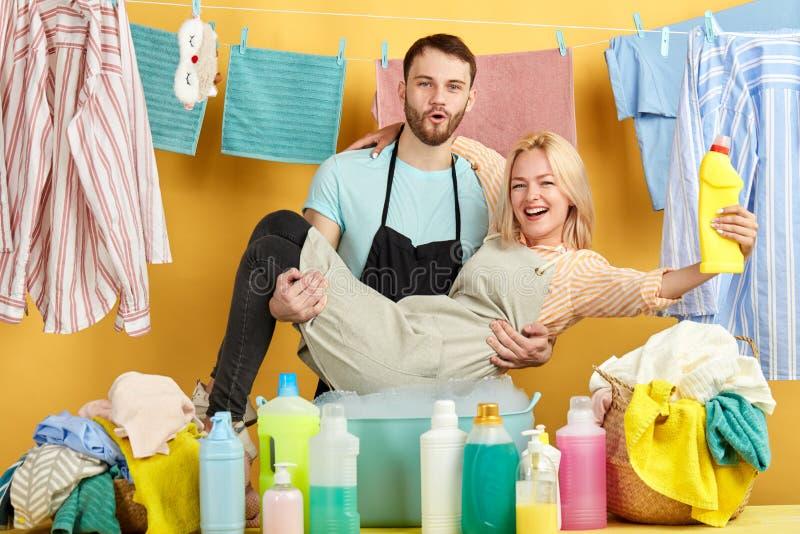 Grappig jong paar die pret hebben terwijl het doen van huishoudenkarweien stock afbeeldingen