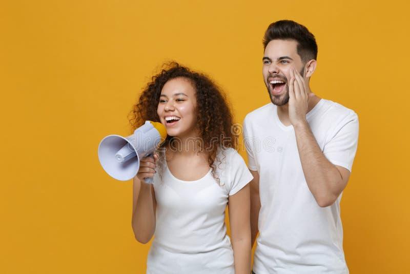 Grappig jonge vrienden Europees man african american meisje in witte t-shirts die geïsoleerd zijn op gele achtergrond stock afbeeldingen