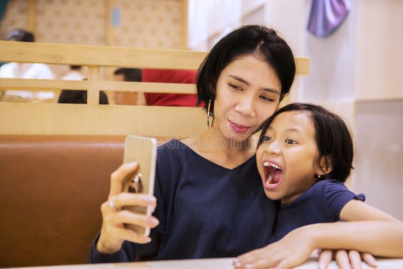 Grappig kind die foto selfie met haar moeder nemen stock foto