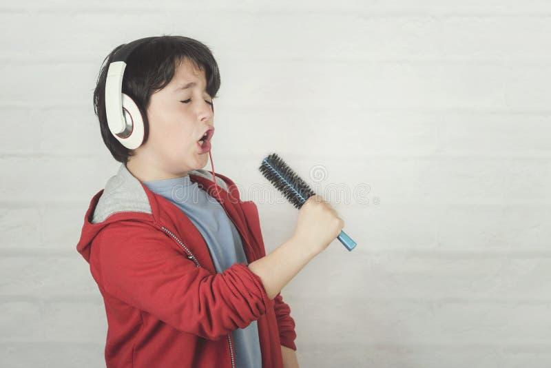 Grappig kind in hoofdtelefoons die met haarborstel zingen royalty-vrije stock foto's