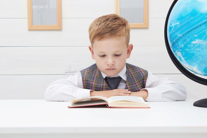 Grappig Kind in school weinig jongen met Boek, Kinderenonderwijs stock foto's