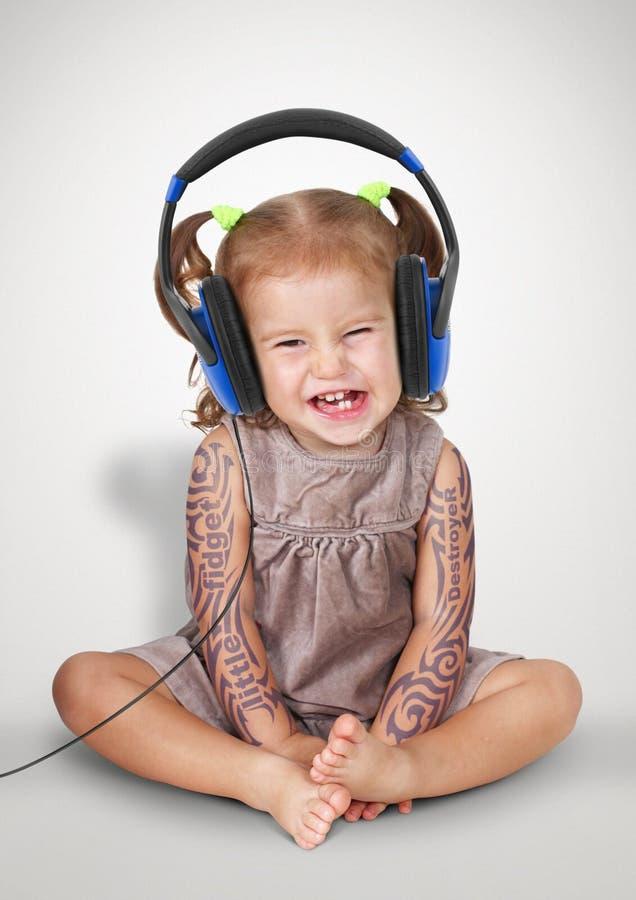 Grappig kindmeisje met tatoo het luisteren muziek met hoofdtelefoons royalty-vrije stock afbeelding