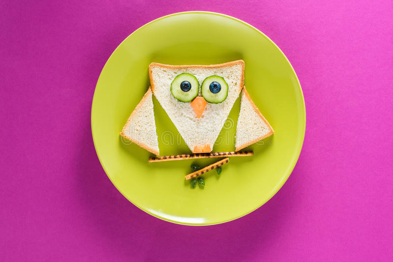 Grappig kleurrijk ontbijt voor kind in vorm van uil op groene plaat stock fotografie