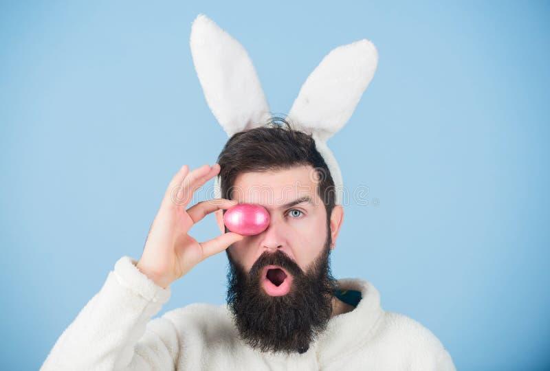 Grappig konijntje met baard en snorgreep roze ei Gebaarde dwaze het konijntjesoren van de mensenslijtage Pasen-symboolconcept MIJ royalty-vrije stock afbeeldingen