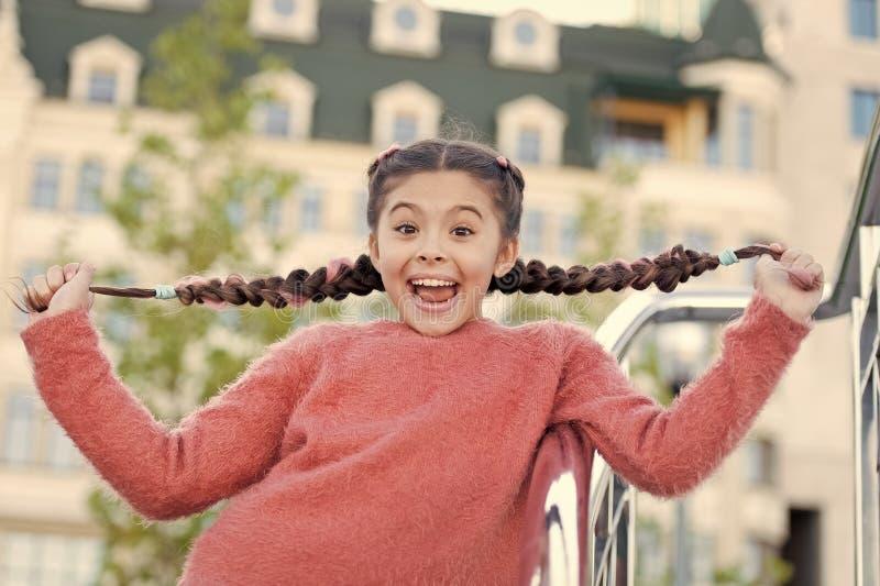 Grappig leuk meisje in stad die haar lange mooie vlechten tonen Speelmeisje met zeer gelukkige glimlach op haar gezicht Het hebbe stock afbeelding