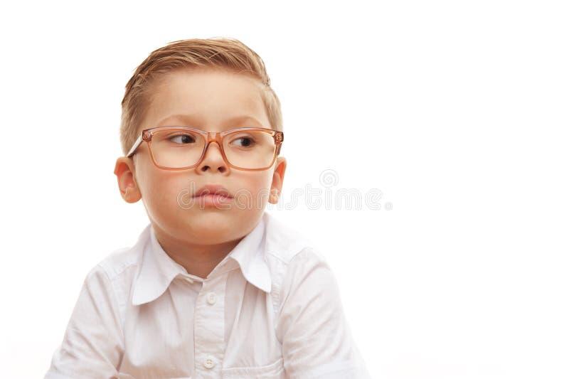 Grappig leuk weinig jongen in glazen die op witte achtergrond stellen royalty-vrije stock afbeelding