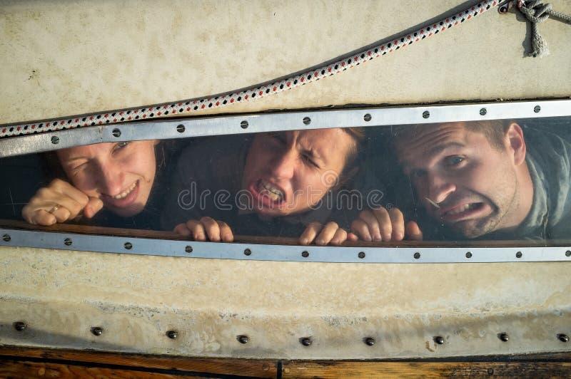 Grappig mannelijk en vrouwelijk makend grimas, het foolishing, c als zijn zij zeer het boze kijken door venster stock afbeeldingen