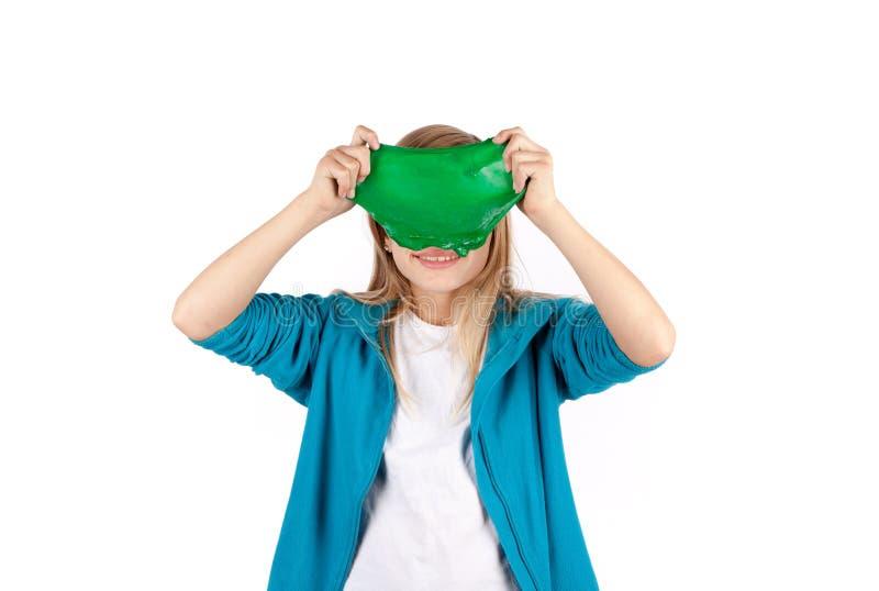 Grappig meisje die een groen slijm houden stock afbeeldingen