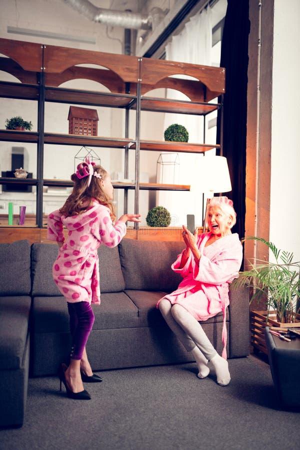 Grappig meisje die en modeshow voor haar mooie oma stellen maken royalty-vrije stock afbeeldingen