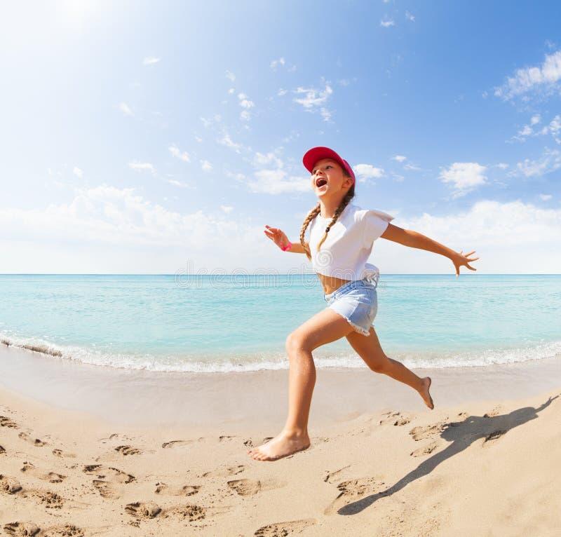 Grappig meisje die en op strand lopen springen stock fotografie