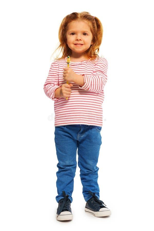 Grappig meisje die gele tandenborstel houden stock afbeeldingen