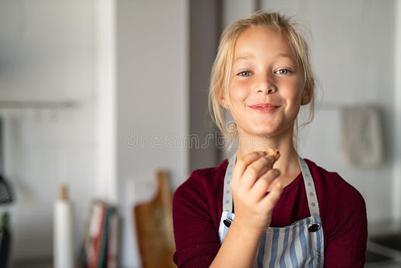 Grappig meisje die in schort met de hand gemaakt koekje eten royalty-vrije stock foto's