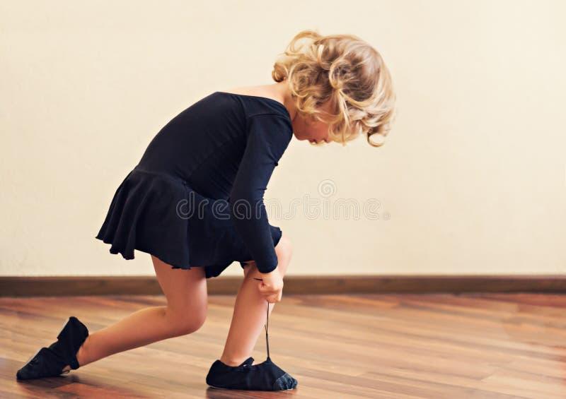 Grappig meisje gezet op schoenen voor dans stock afbeelding