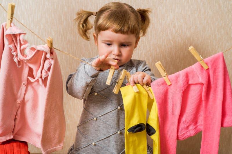 Grappig meisje met clothespin en de clothesline Babyroze kleren droog op touw baby hangt gele sokken aan en een roze trui royalty-vrije stock afbeelding