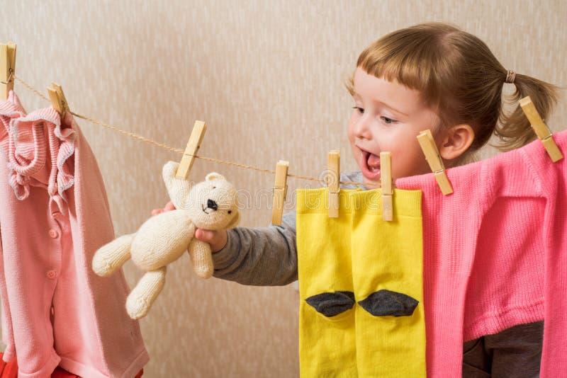 Grappig meisje met clothespin en de clothesline Babyroze kleren droog op touw baby hangt gele sokken aan en een roze trui royalty-vrije stock foto