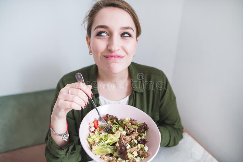 grappig meisje met een plaat van salade in hun handen Krachtig voedsel Een grappige vrouw eet een salade royalty-vrije stock fotografie