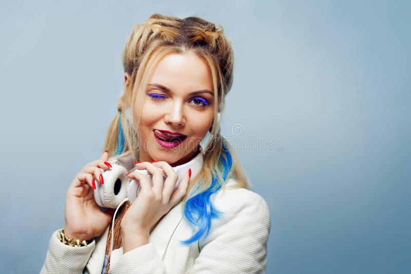 Grappig meisje met gekleurde bundels in haar haar Het luisteren muziek en het tonen van tong royalty-vrije stock fotografie