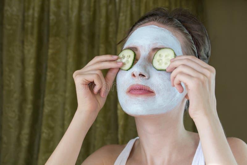 Grappig meisje met masker die komkommer twee op de ogen houden stock afbeelding