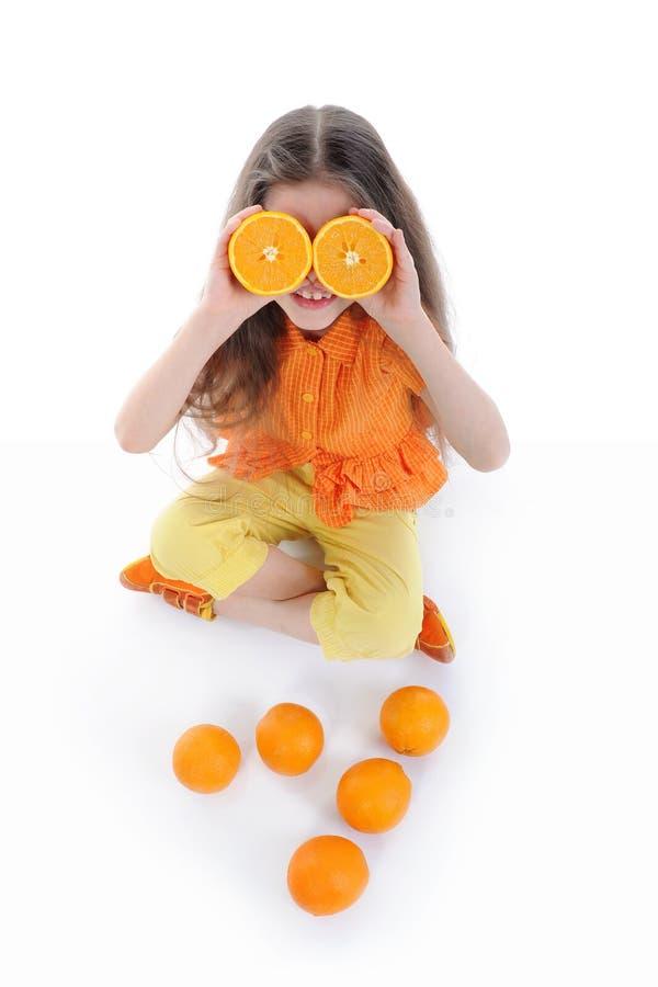Grappig meisje met sinaasappelen. stock afbeelding