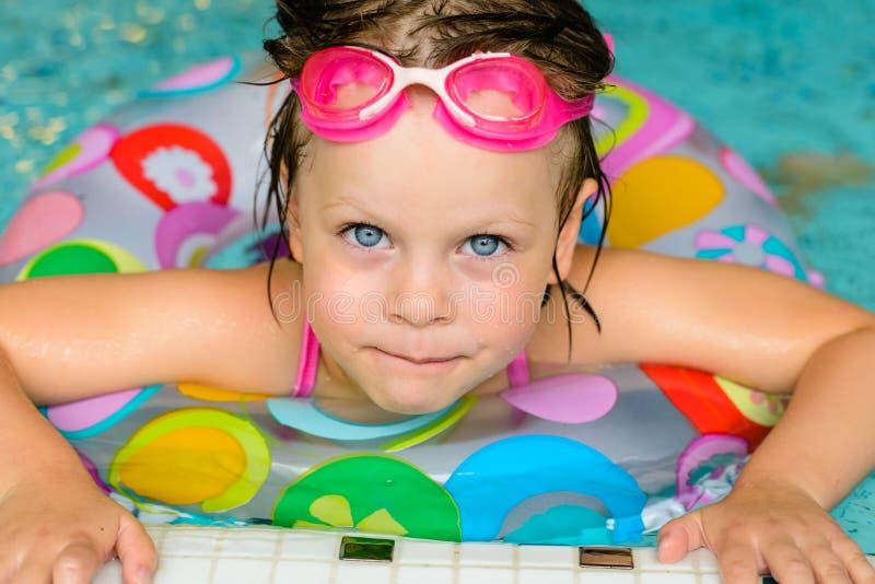 Grappig meisje in roze beschermende brillen in het zwembad royalty-vrije stock afbeelding