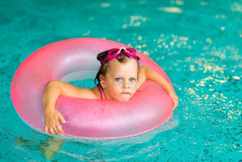 Grappig meisje in roze beschermende brillen in het zwembad stock afbeelding