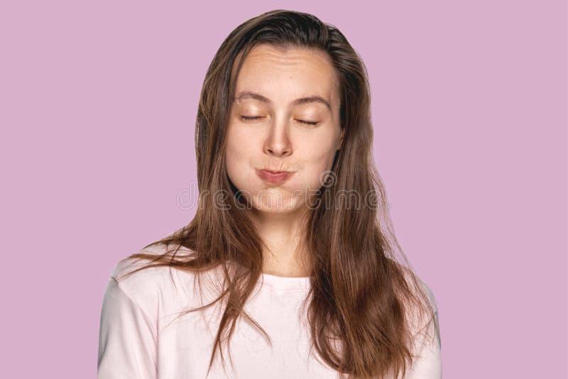 Grappig mooi meisje die uit haar wangen puffen tegen de achtergrond van de lavendelstudio Headshot van het charmeren van rode hai stock fotografie