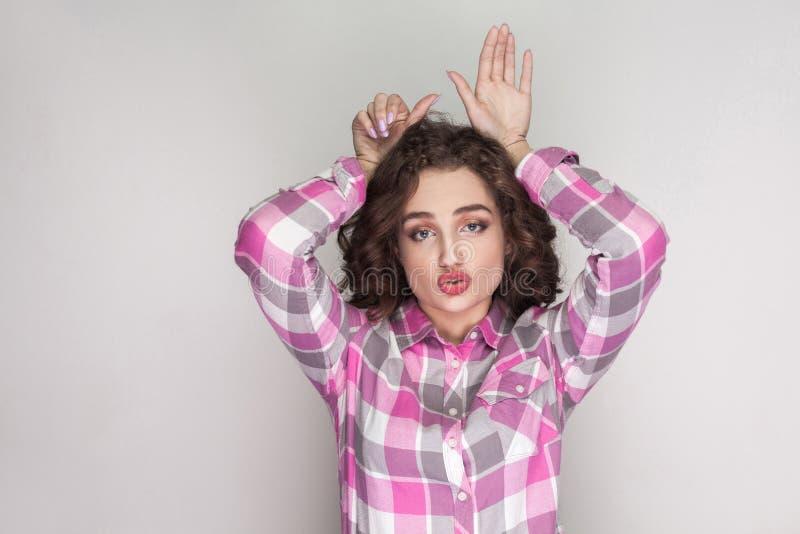 Grappig mooi meisje met roze geruit overhemd, krullend kapsel stock afbeelding
