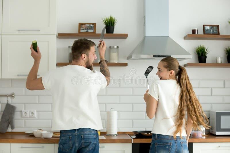 Grappig paar die pret het koken in keuken hebben samen, achtermening stock fotografie