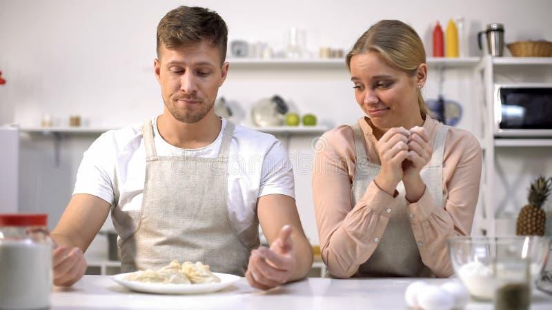Grappig paar die ruw deeg, slechte kooktoestellen, kokende cursussen voor amateurs bekijken royalty-vrije stock afbeeldingen