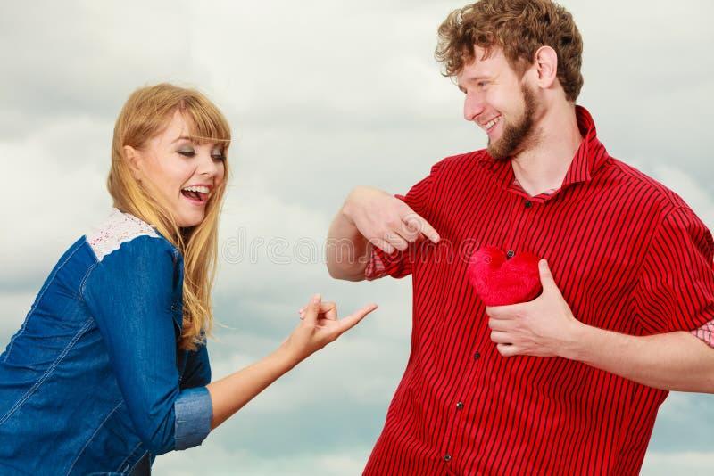 Grappig paar in liefde het spelen met rood hart openlucht royalty-vrije stock afbeeldingen