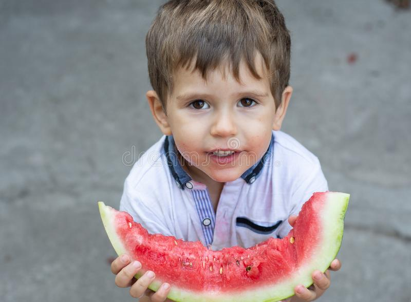 Grappig portret die van een ongelooflijk mooie jongen, watermeloen, gezonde fruitsnack eten, royalty-vrije stock foto's