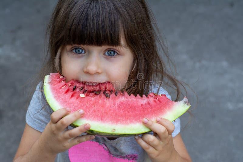 Grappig portret die van een ongelooflijk mooie meisje blauwe ogen, watermeloen, gezonde fruitsnack eten, stock afbeelding