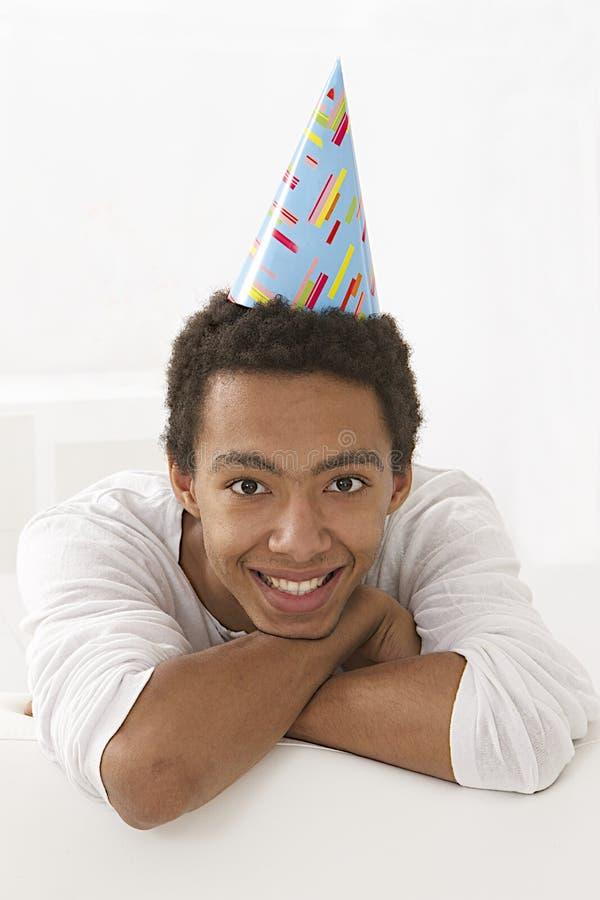 Grappig portret van een aardige mulat jonge mens met een partijhoed stock fotografie